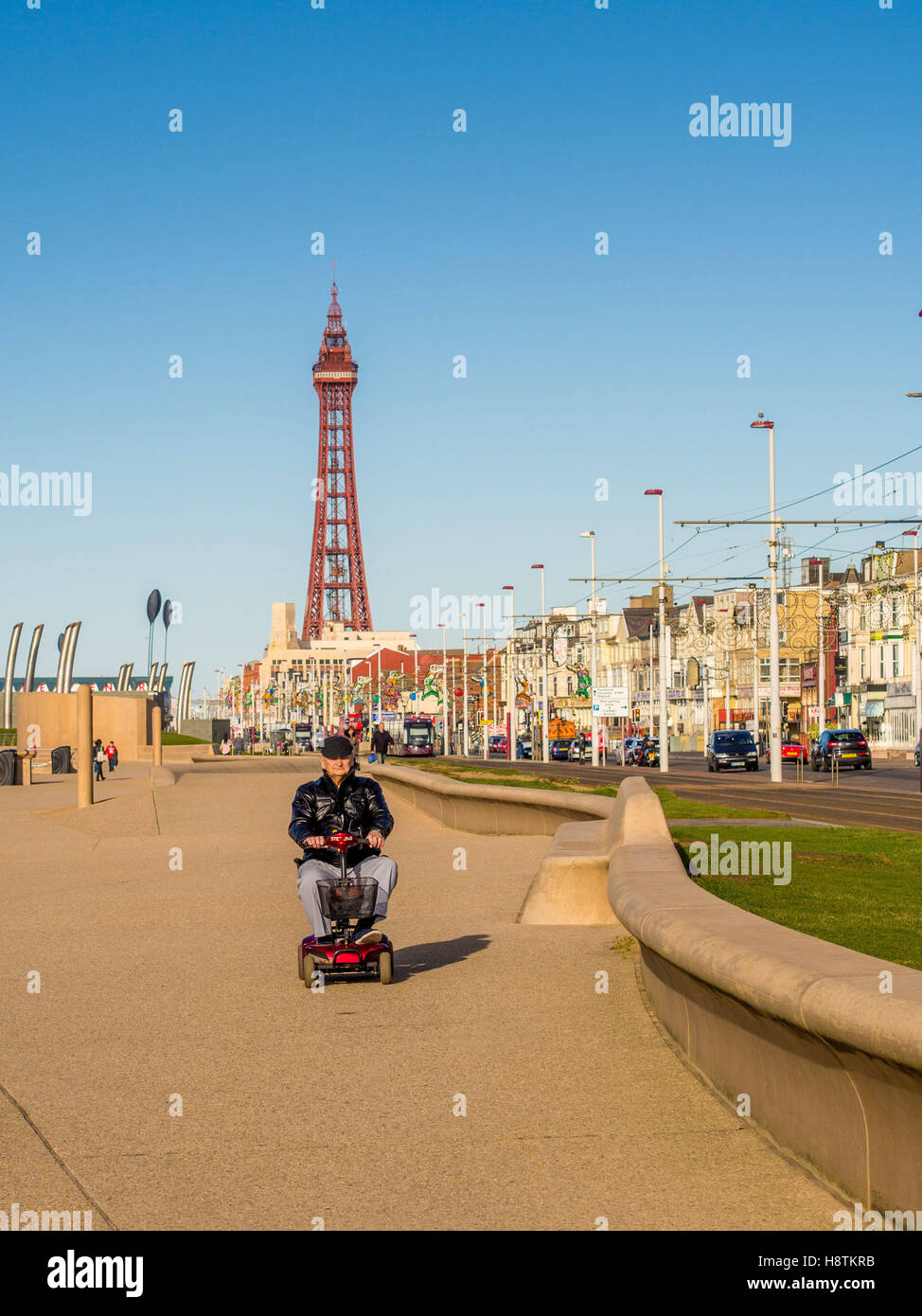 Old man riding electric mobility scooter along Blackpool Promenade with Blackpool Tower in background, Lancashire, - Stock Image