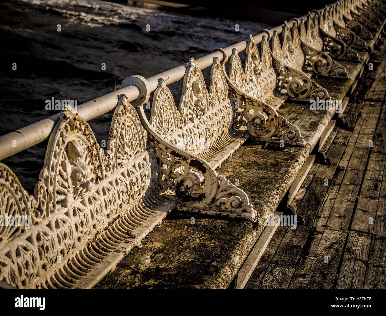 Traditional cast iron seats in a state of disrepair on Pier, Blackpool, Lancashire, UK. - Stock Image
