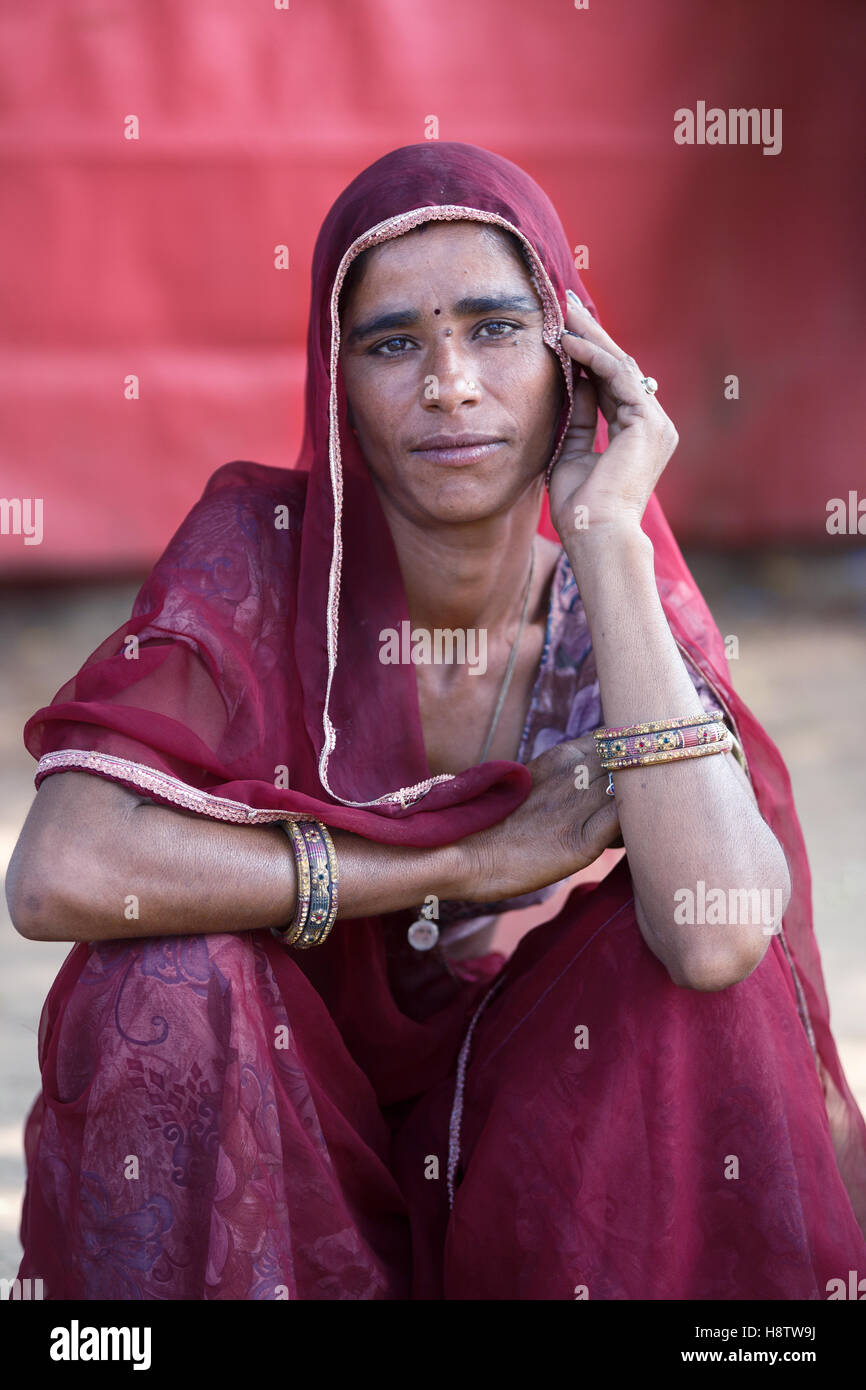 indian woman dressed in traditional scarf and sari, sits in front of the red tent and looks at the camera Stock Photo