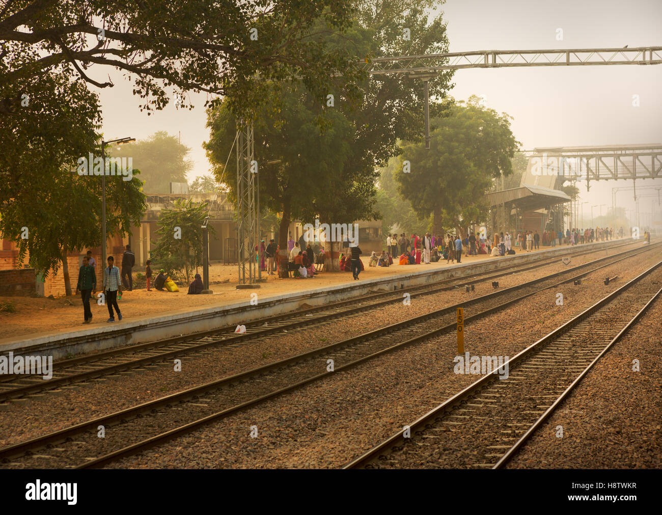 People wait for the train in a station near Delhi.Railway is most common transportation way in India. - Stock Image