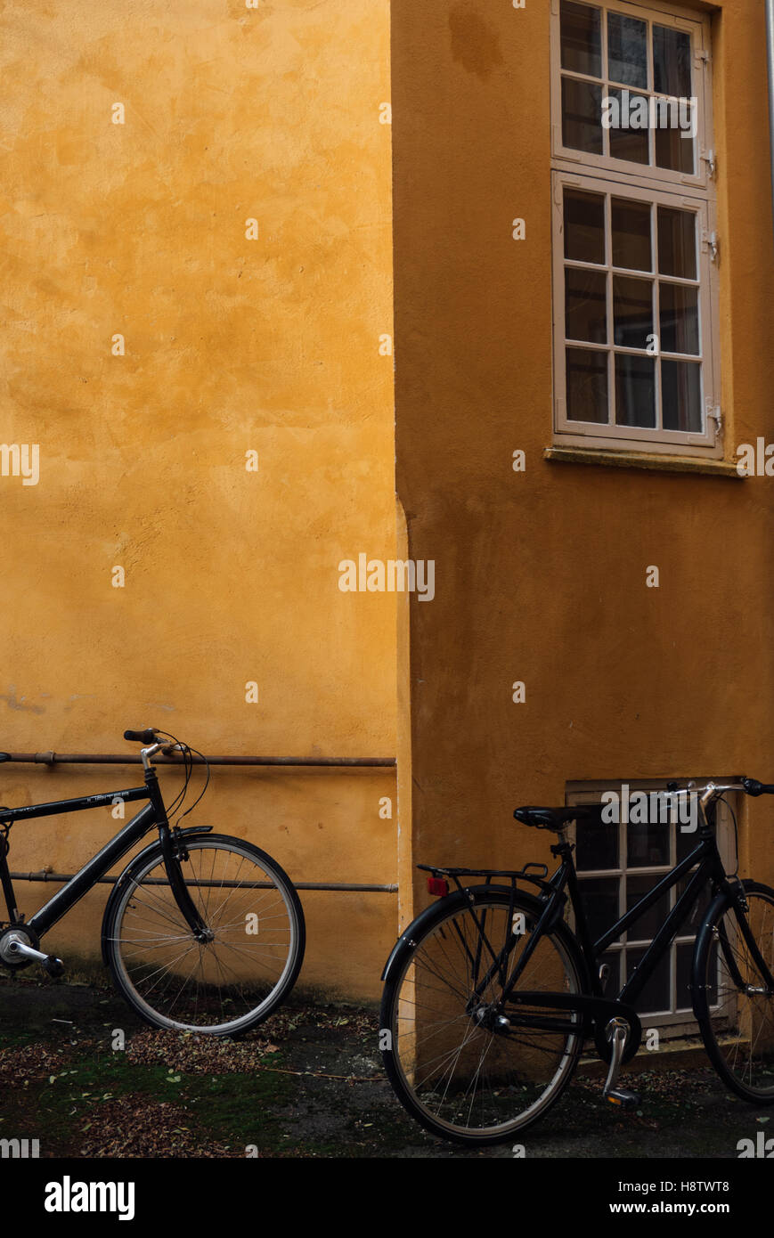 Bikes parked by a yellow building in Copenhagen - Stock Image