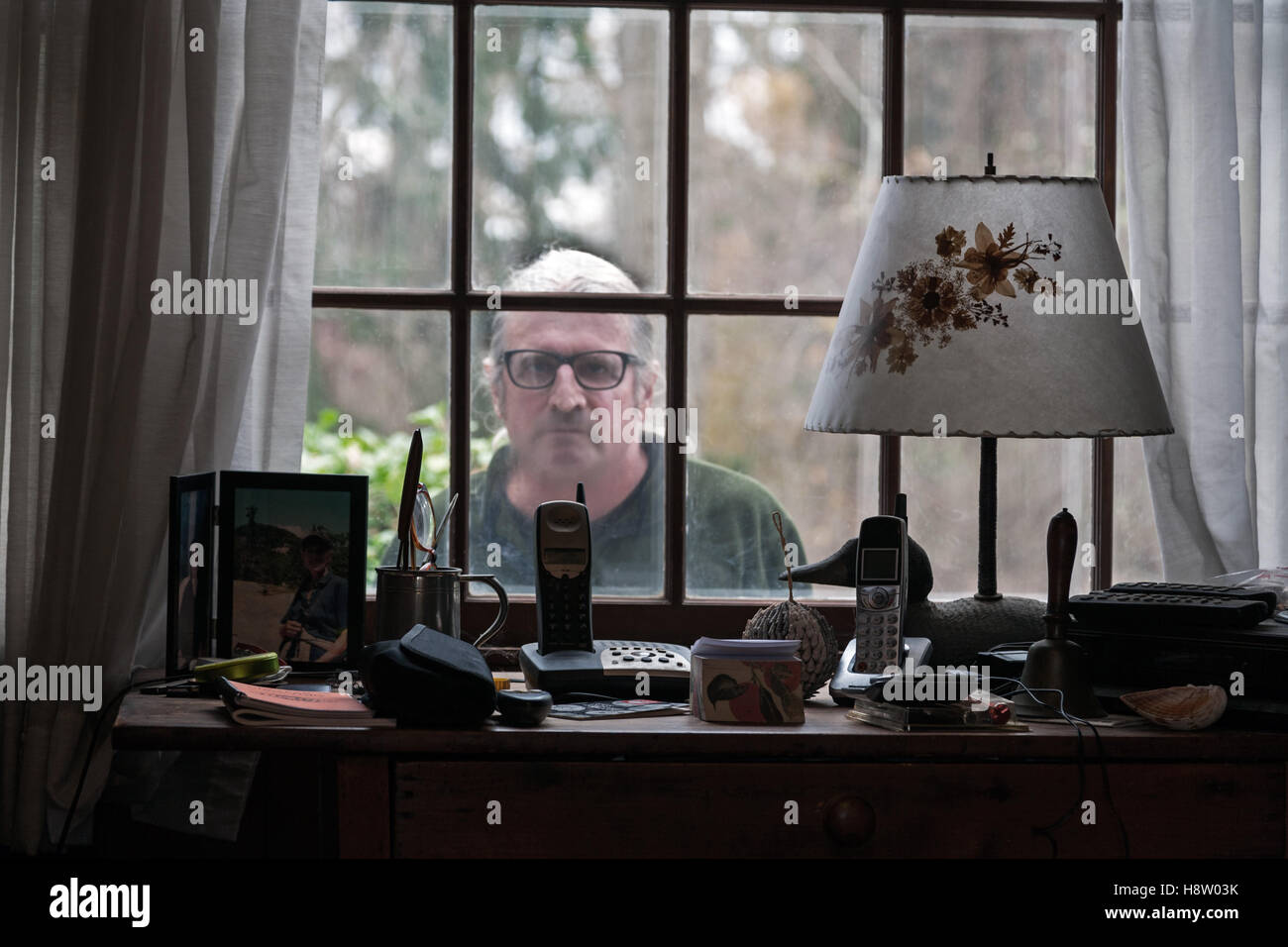 Mid-Adult Man Peering through House Window - Stock Image