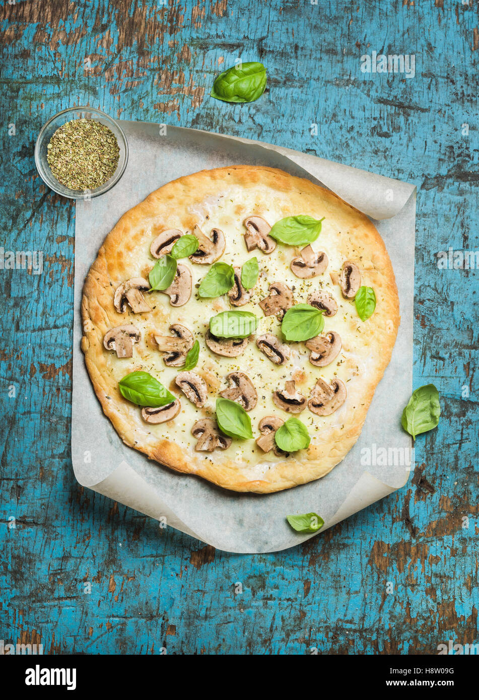 Homemade mushroom pizza with basil leaves over blue wooden background - Stock Image