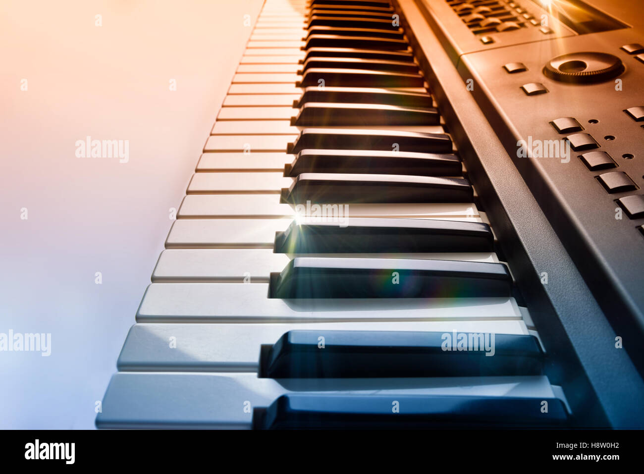 Synthesizer keyboard with shine and blue red gradient. Horizontal Composition.Elevated side view - Stock Image