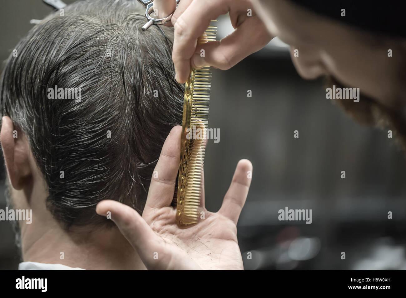 Doing haircut in barbershop - Stock Image