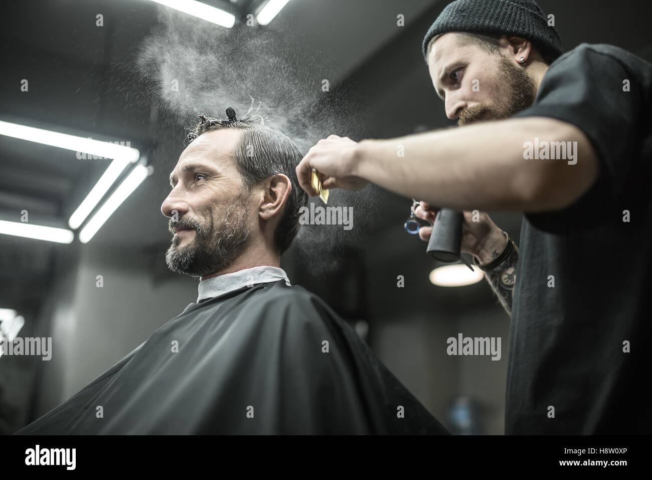 Barber is using spray bottle - Stock Image
