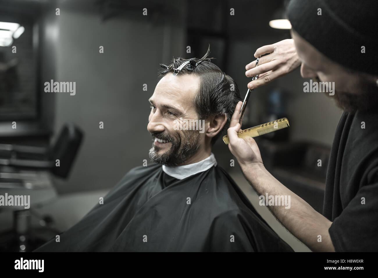 Cutting hair in barbershop - Stock Image