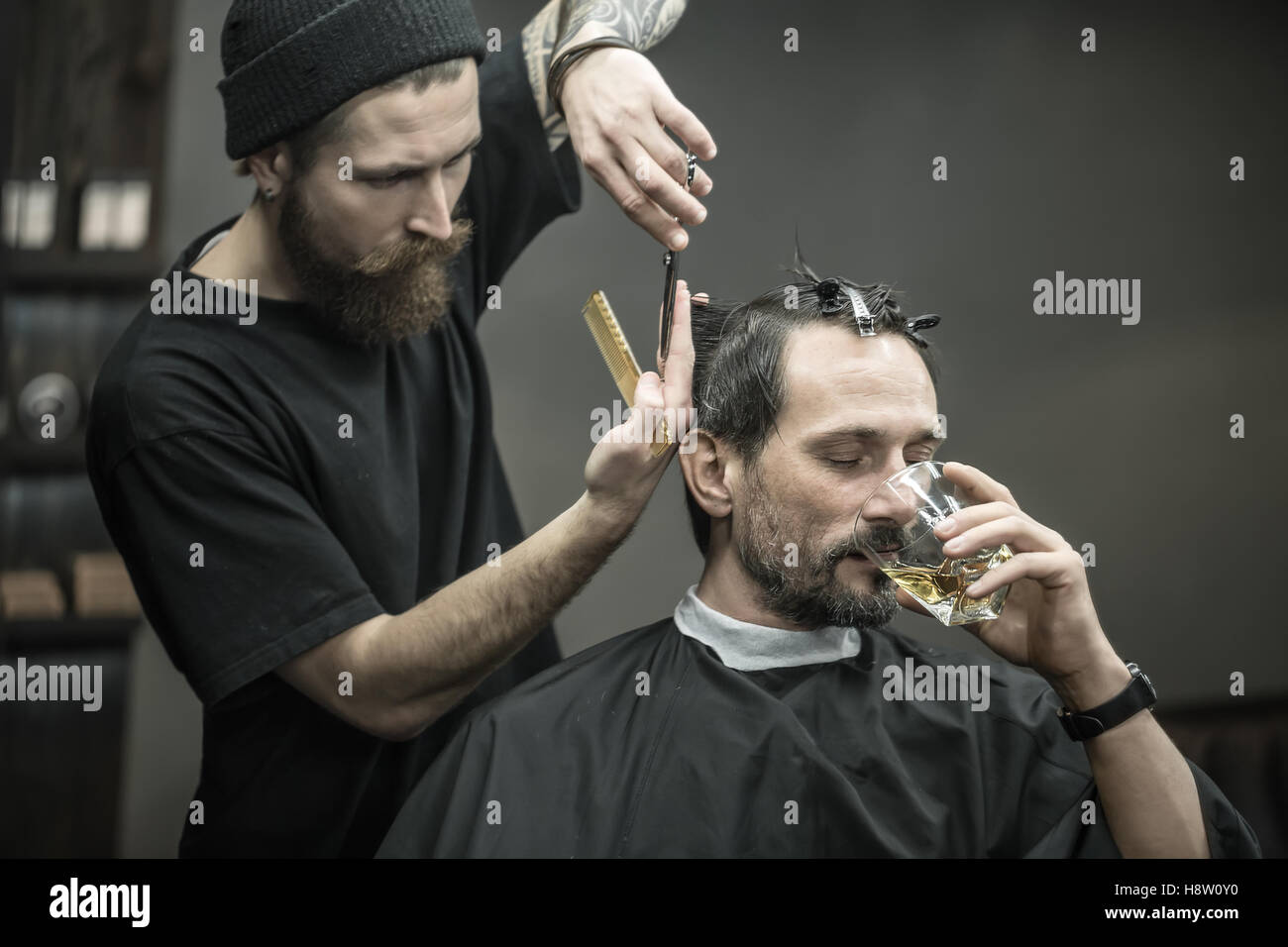 Drinking and cutting in barbershop - Stock Image