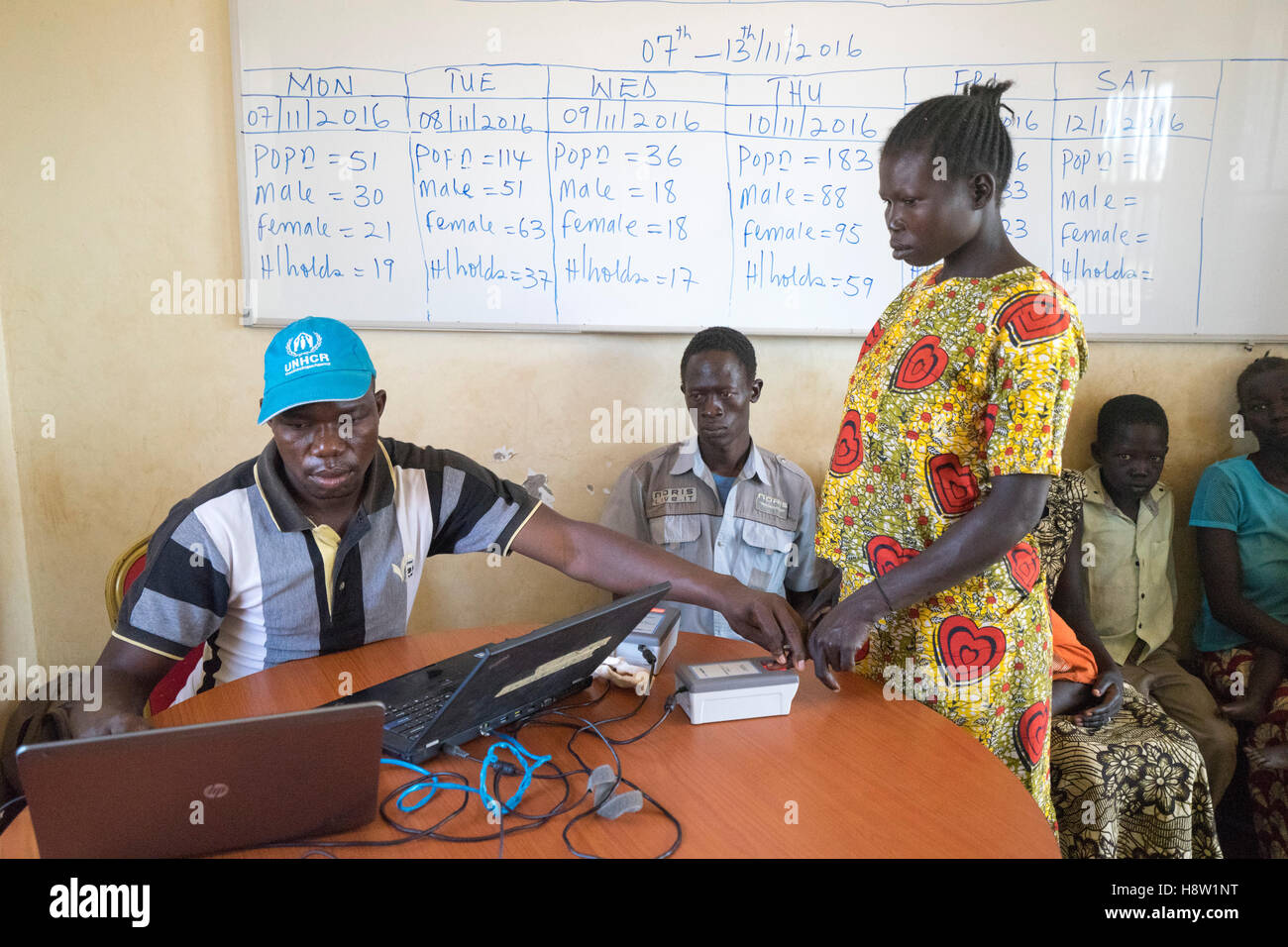 On the boarders of South Sudan and Uganda. UNHCR worker taking fingerprints, before the refugee is allowed into - Stock Image