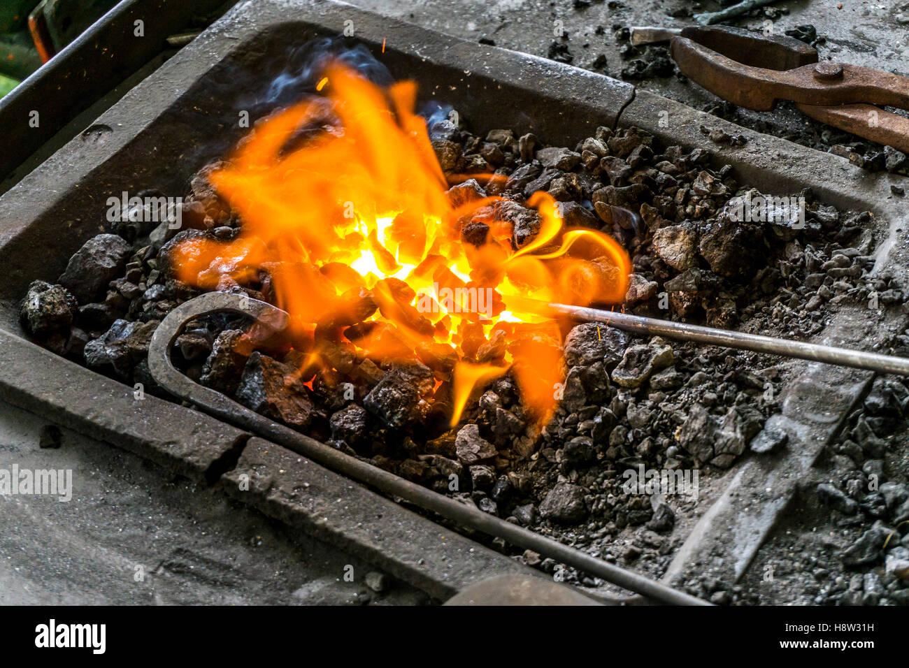 Feuer, Glut in einer Schmiede, erhitzen von einer Metallstab, um ihn später zu schmieden, Holzkohlefeuer, - Stock Image