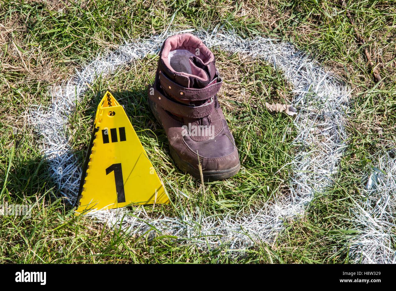 Spurensicherung, bei einem Unfall gefundener Schuh eines Opfers, markiert mit einer Spurentafel und einem weissen - Stock Image