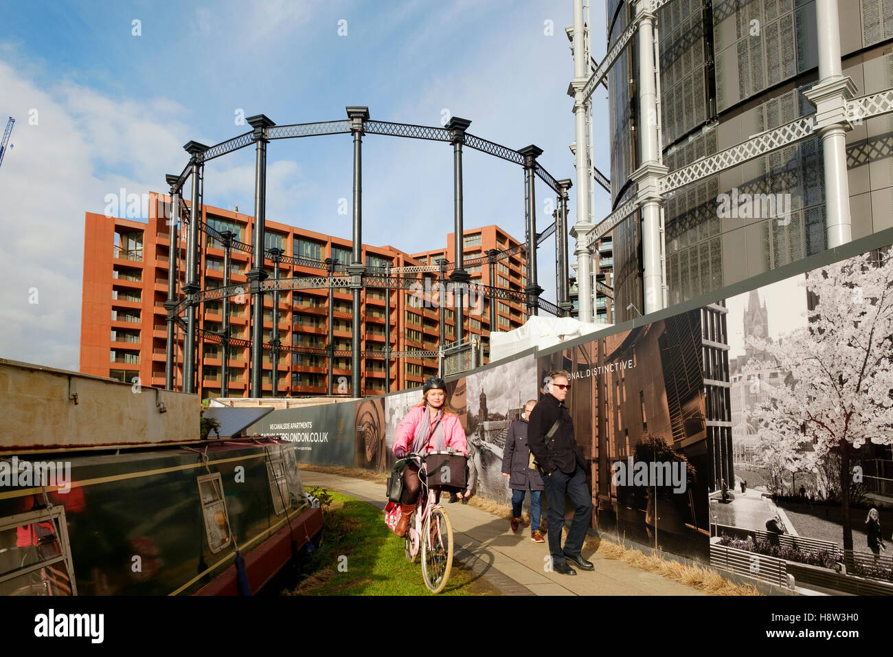 People on the towpath of the Regents Canal at St Pancras passing the Gasholder Park development. Kings Cross, London. - Stock Image