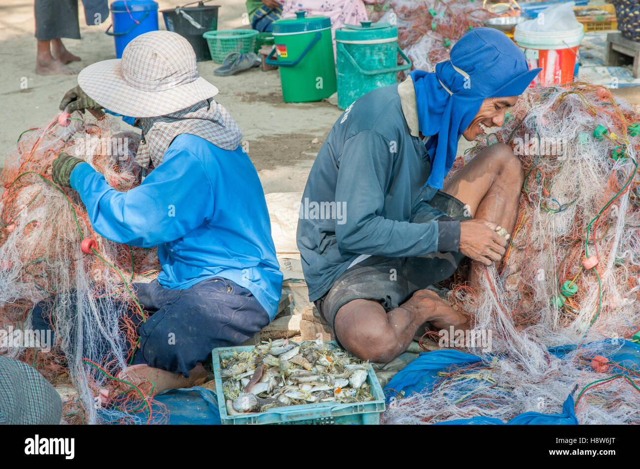 Thai people collect catch of sea food from fishing net in a village south of Hua Hin - Stock Image