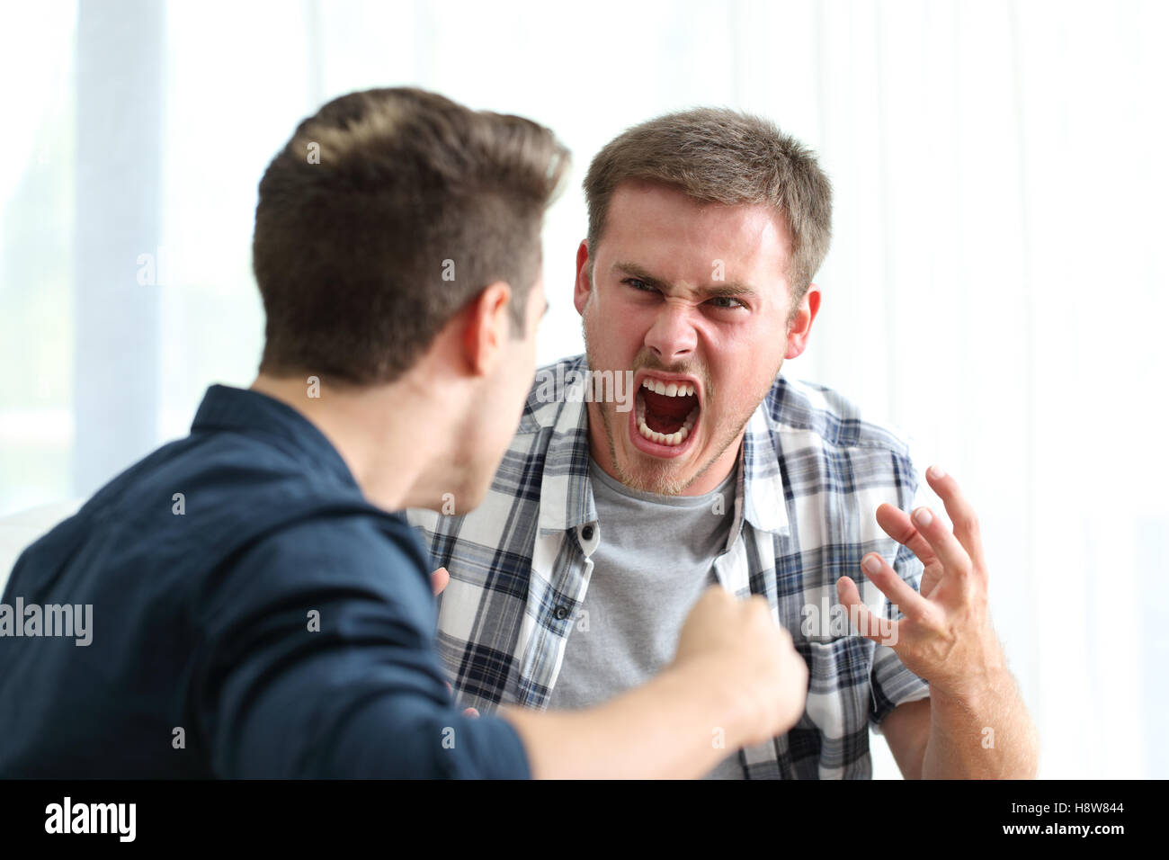 Two angry friends or roommates arguing and threatening in the living room at home - Stock Image