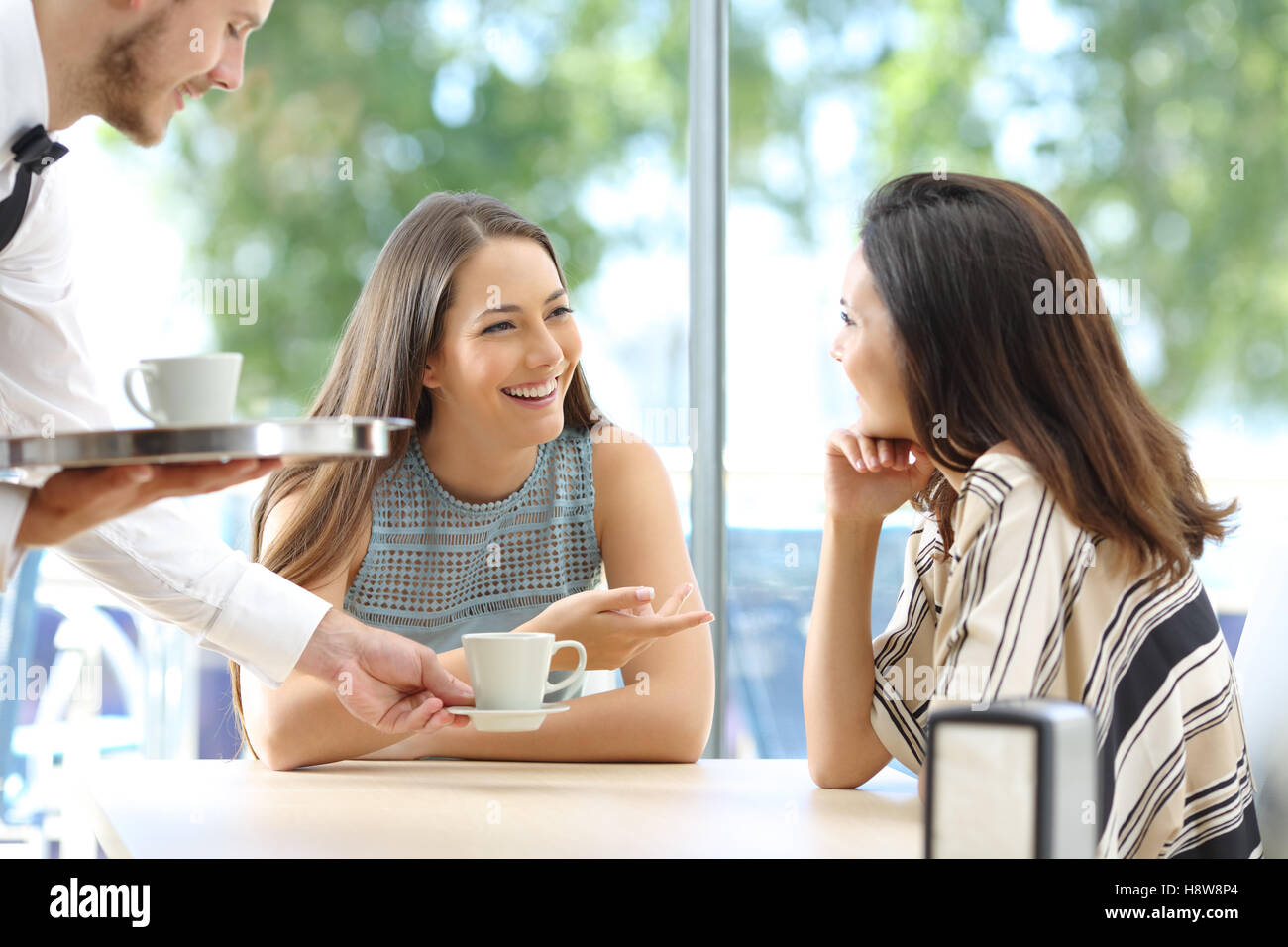 Happy friends talking looking each other sitting in the table of a bar with the waiter serving cups of coffee - Stock Image