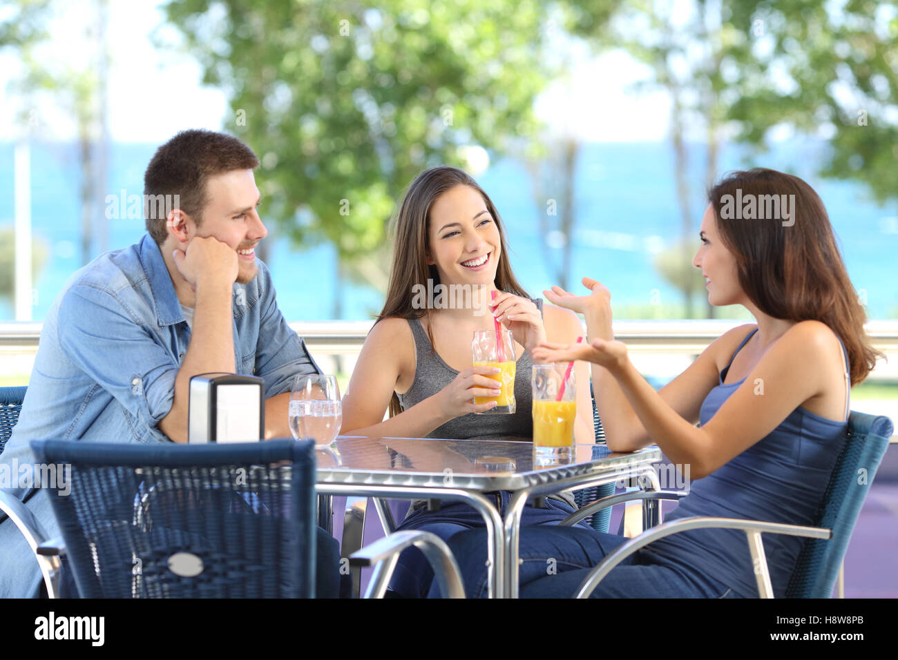 Group of three happy friends talking and refreshing with cold drinks in a bar terrace near of the beach - Stock Image