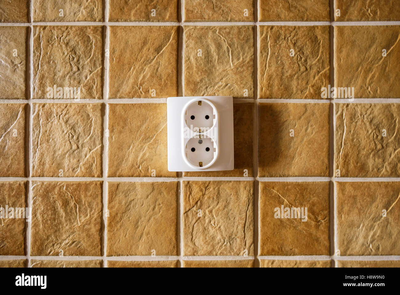 White electric socket on kitchen wall with ceramic tiles pattern texture - Stock Image