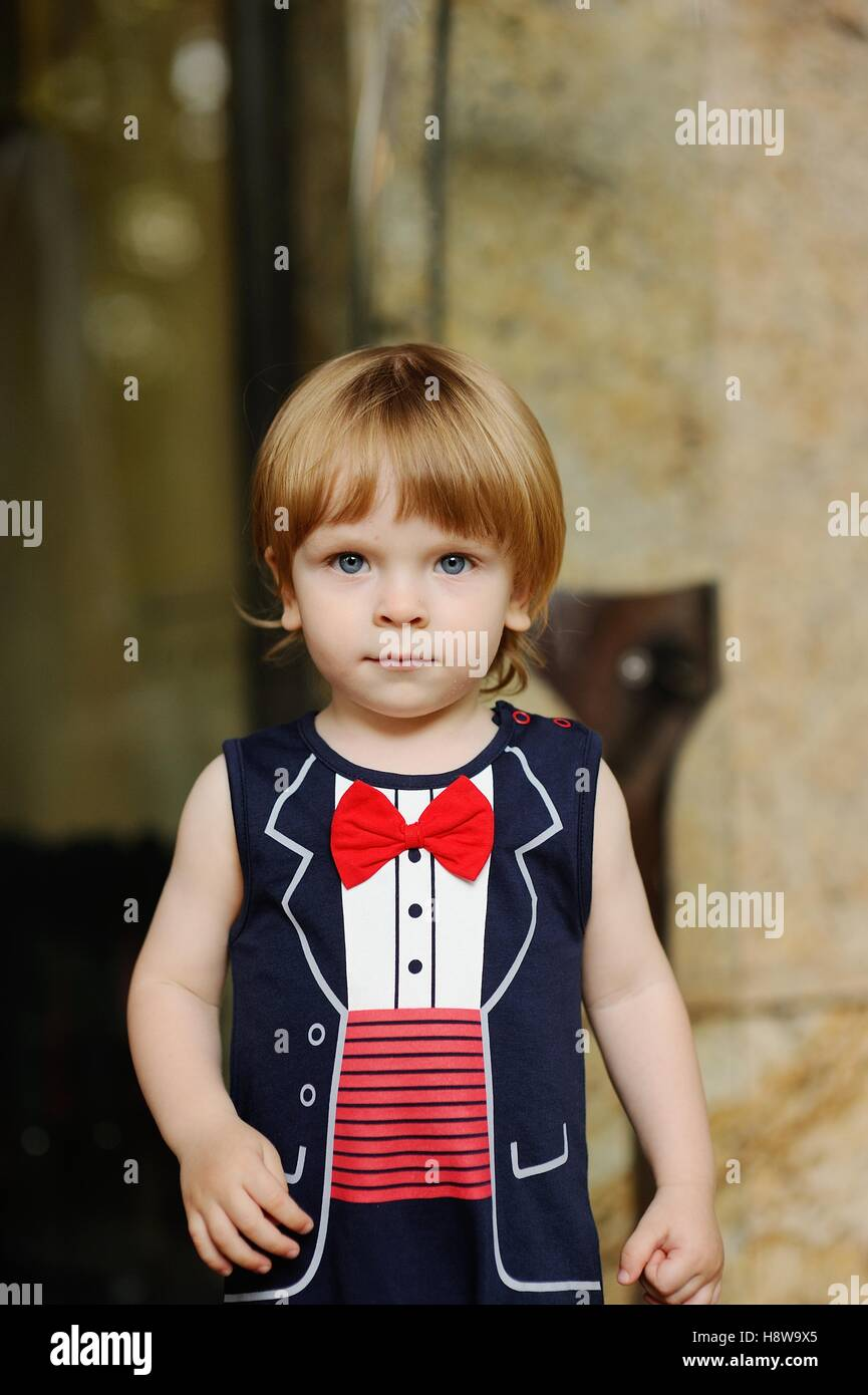 child in a red bow tie on a background of a wall - Stock Image