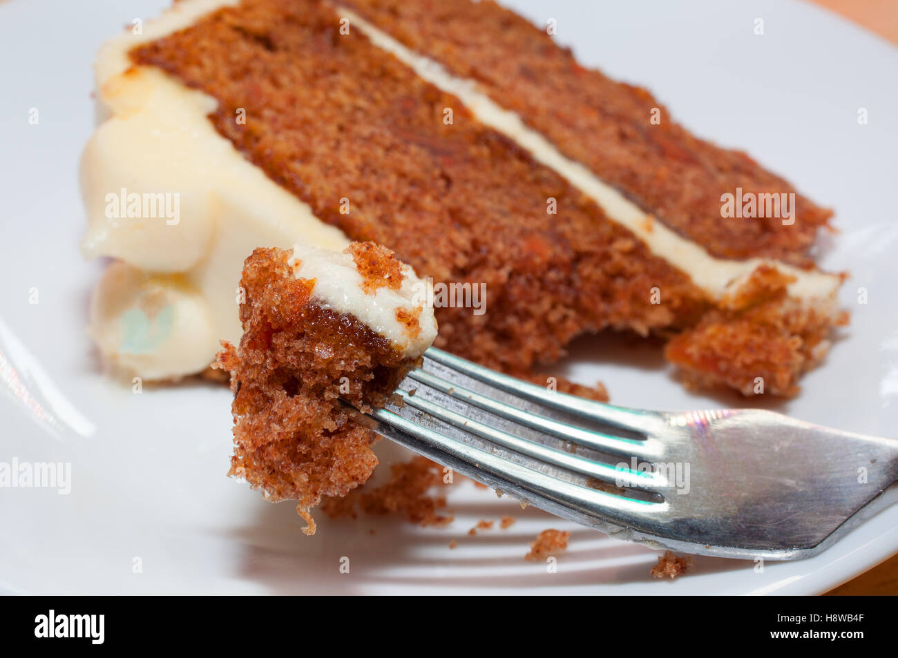 Small slice of carrot cake and a fork on a plate - Stock Image