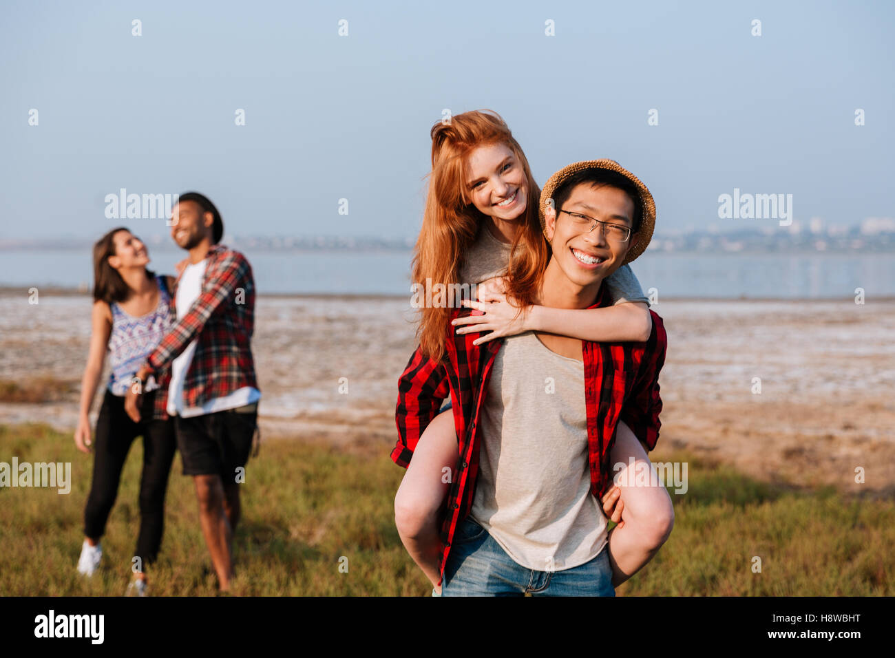 Two happy multiethnic young couples having fun outdoors - Stock Image