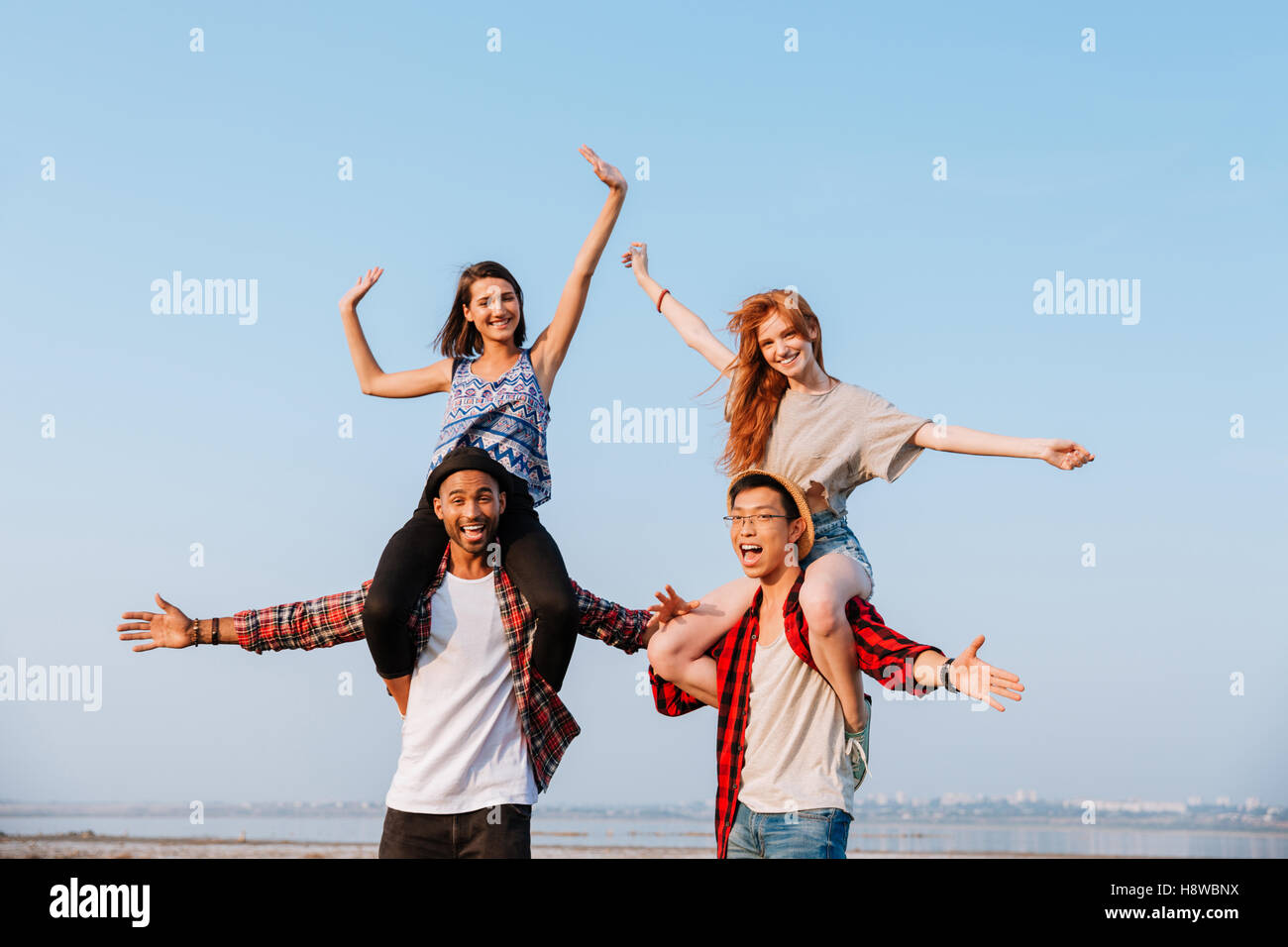 Two happy young women sitting on shoulders of their boyfriends and having fun outdoors - Stock Image