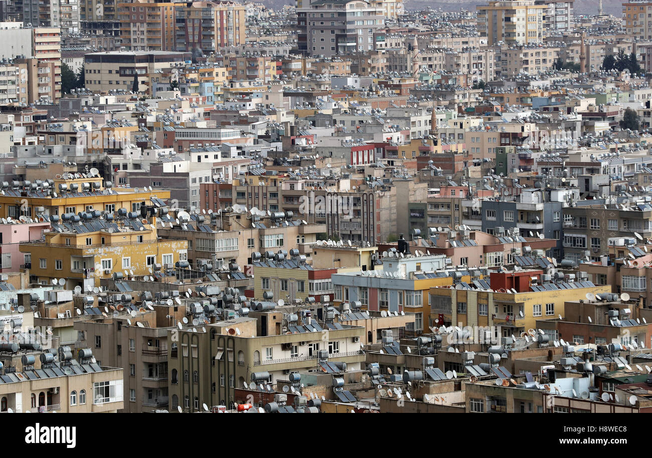 Satellite dishes, water tanks and solar panels on rooftops in the city of Sanliurfa, south eastern Turkey. - Stock Image