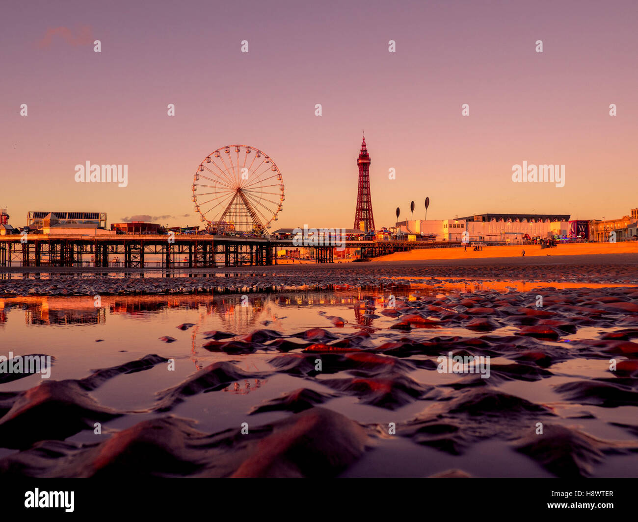 Blackpool Tower and Central Pier with reflection in water on beach at sunset, Lancashire, UK. Stock Photo