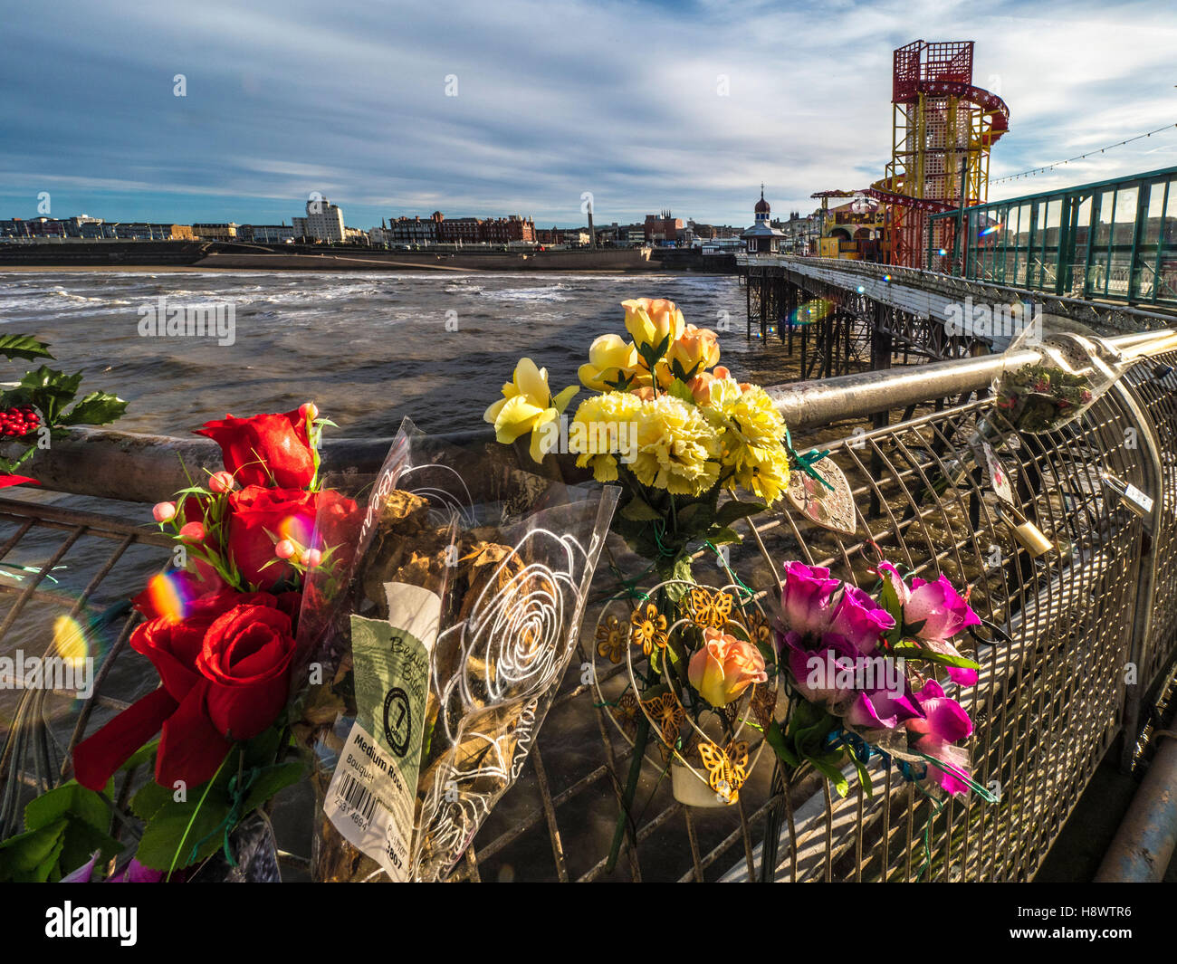 Flowers in memory of dead relatives and friends  tied to railings on North Pier, Blackpool, Lancashire, UK. - Stock Image
