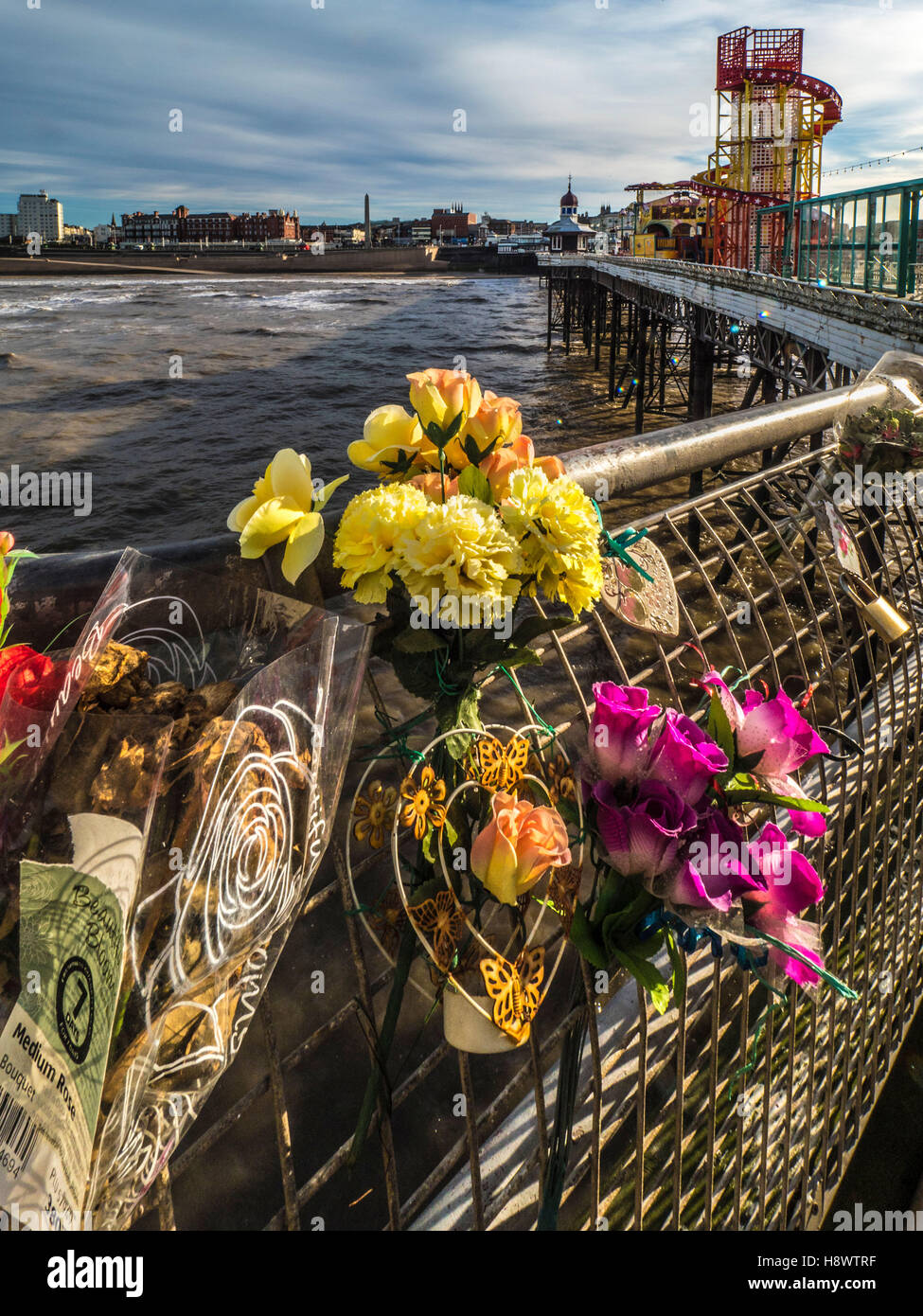 Flowers in memory of dead relatives and freinds tied to railings on North Pier, Blackpool, Lancashire, UK. - Stock Image