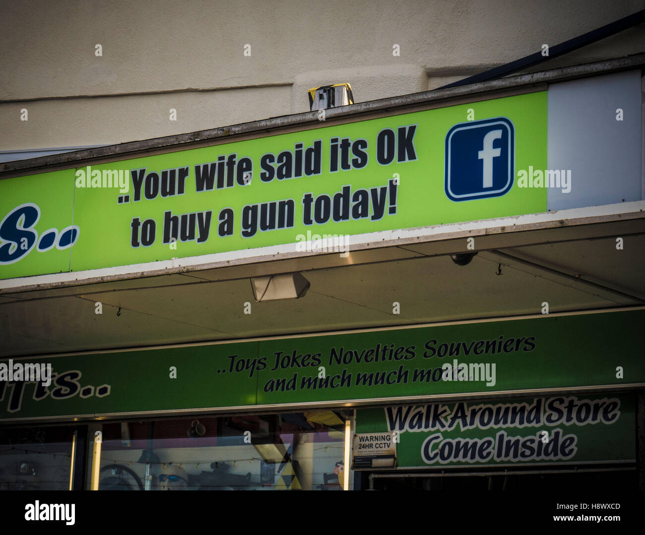 YOUR WIFE SAID ITS OK TO BUY A GUN TODAY sign on shopfront - Stock Image
