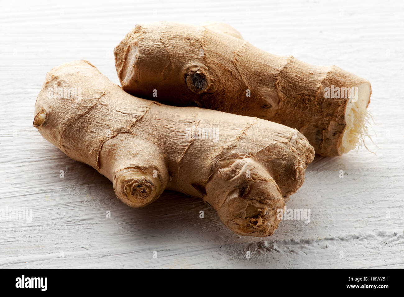 Fresh raw root ginger on a textured white board for use in cooking as a healthy pungent aromatic seasoning - Stock Image