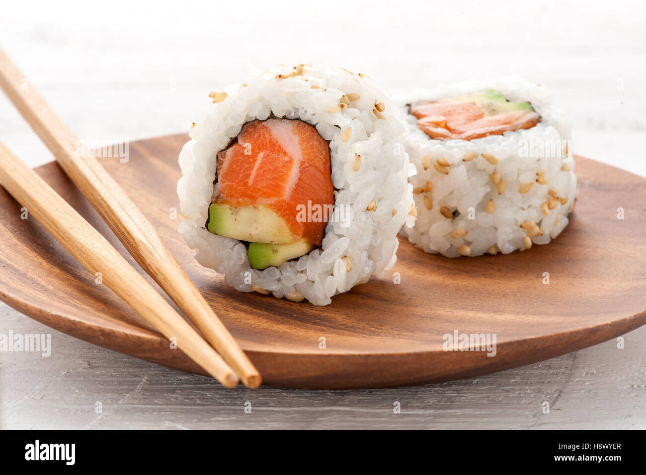 Two fresh salmon and avocado sushi uramaki served on a wooden plate with one standing upright to show the ingredients - Stock Image
