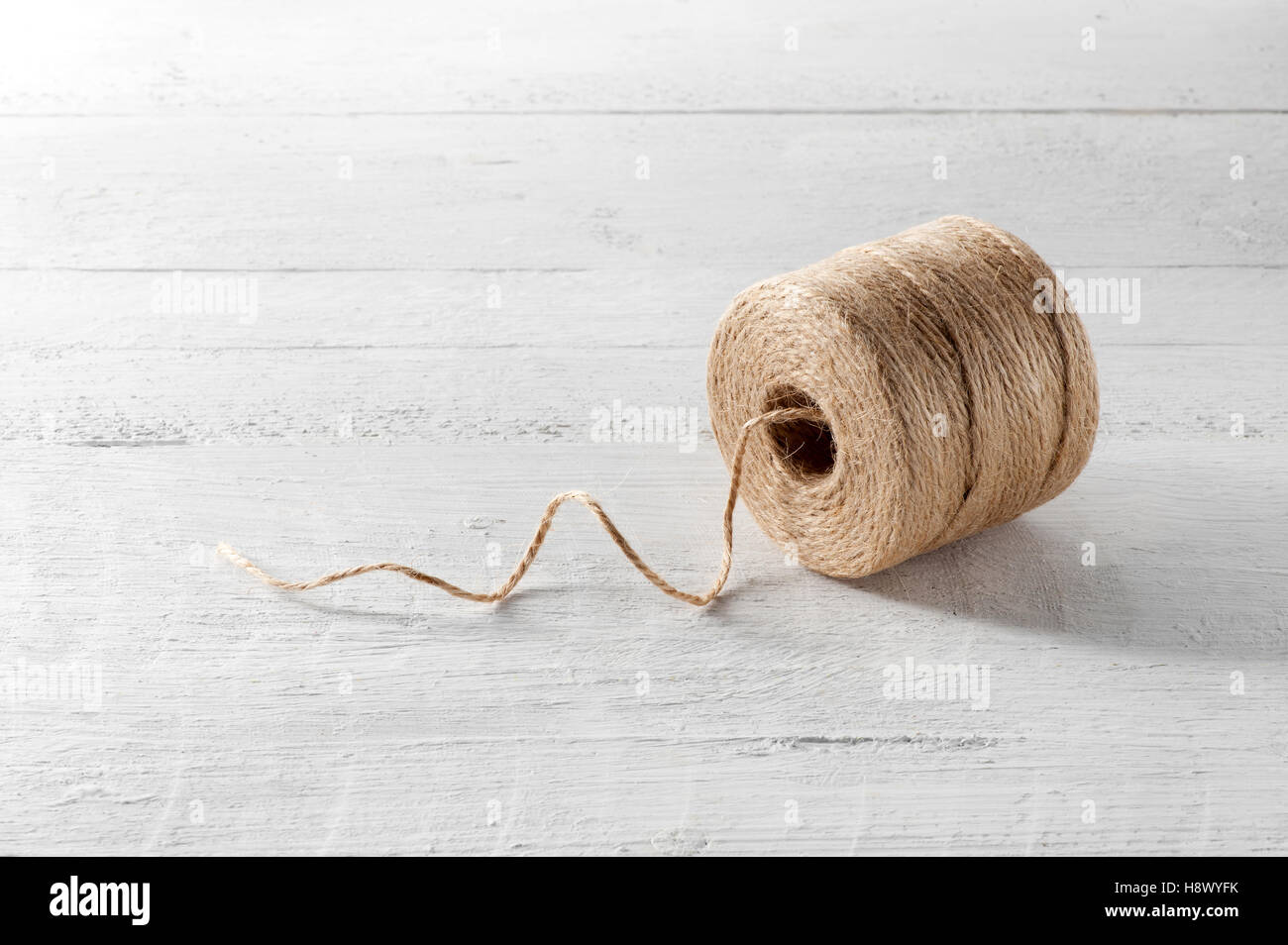 Reel of domestic coarse brown twine made from natural hemp fibers on a white wooden board with a single thread - Stock Image