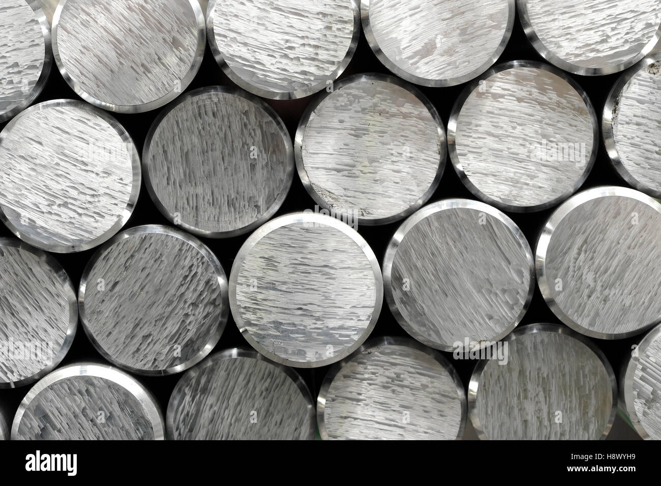 Background texture and pattern of aluminium bars with focus to the cut and bevelled ends of the round metallic silver - Stock Image