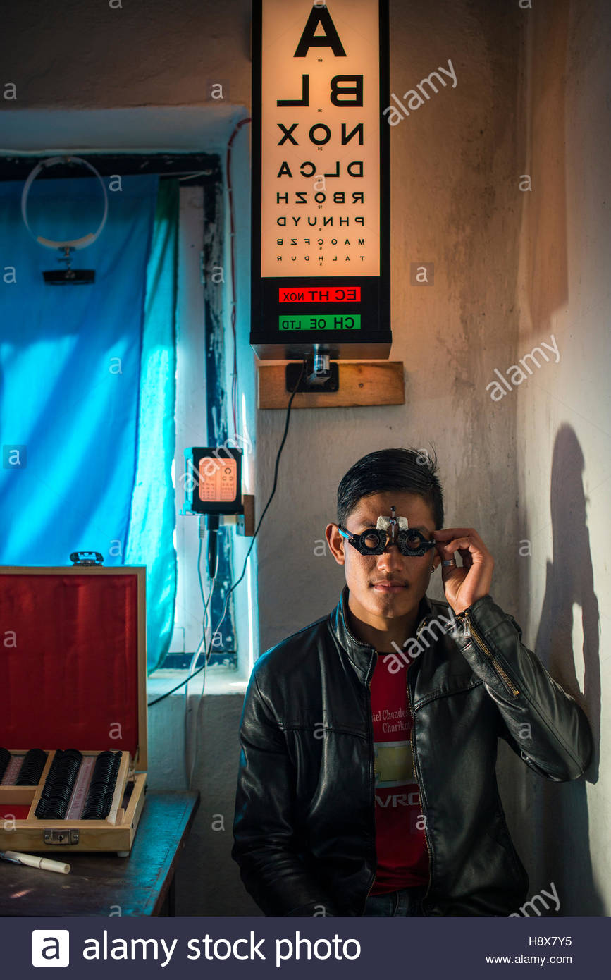 An optometrist tests a patients eyesight in a small hospital in Nepal. - Stock Image