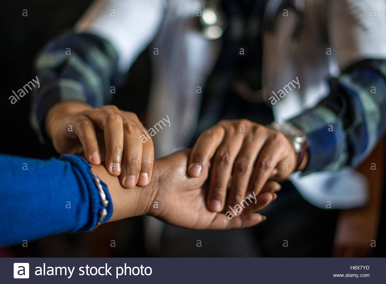 A doctor checks a woman's pulse in a small hospital in Nepal. - Stock Image