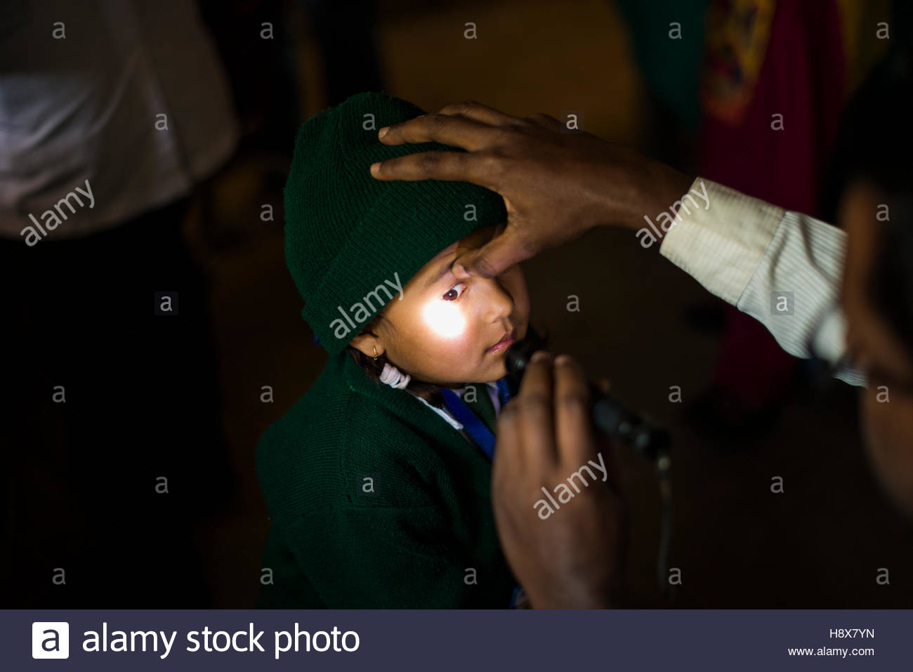 A doctor looking at a baby's eye with a torch in hospital in Nepal. Stock Photo