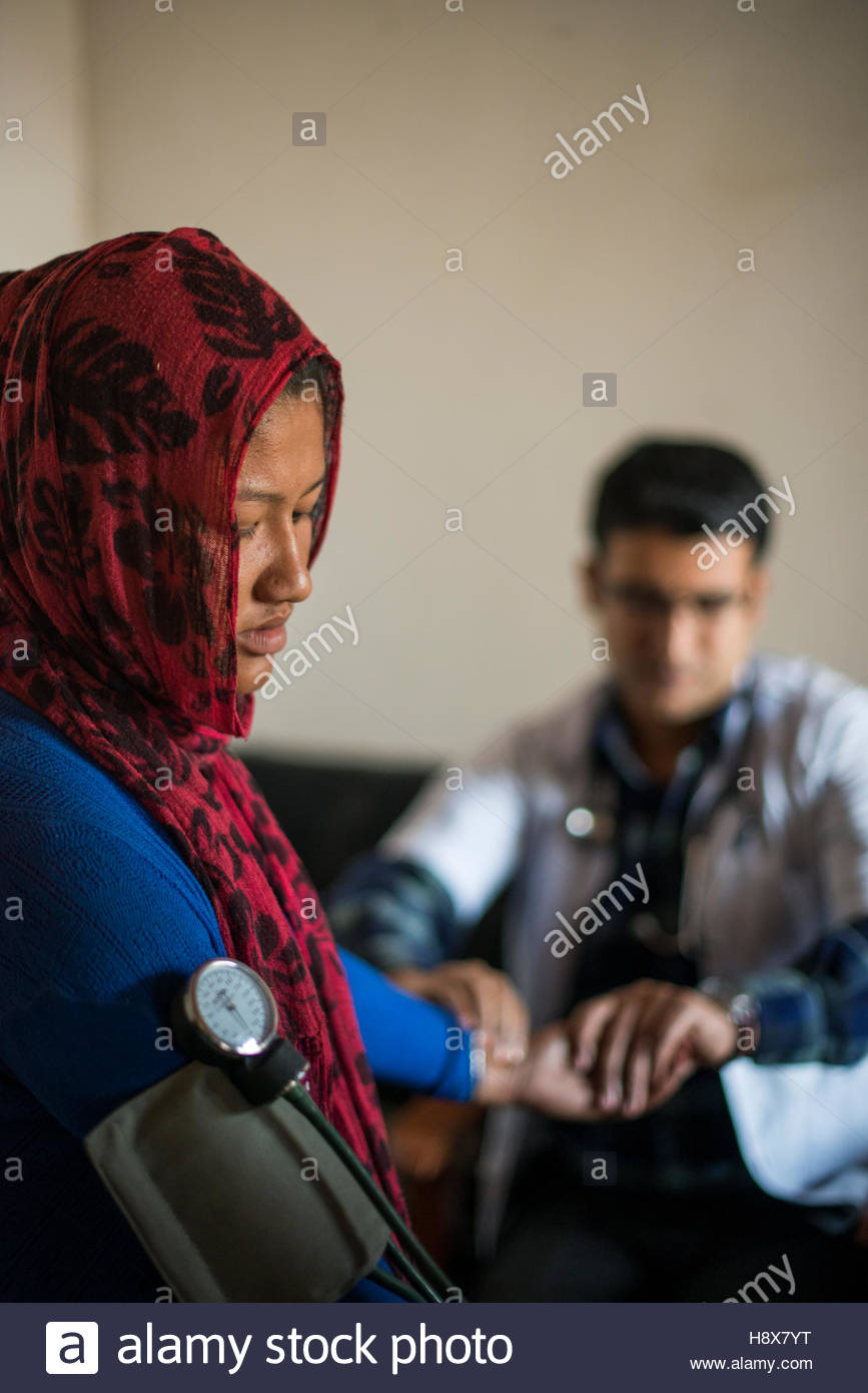Male doctor checking a woman's pulse in hospital in Nepal. - Stock Image