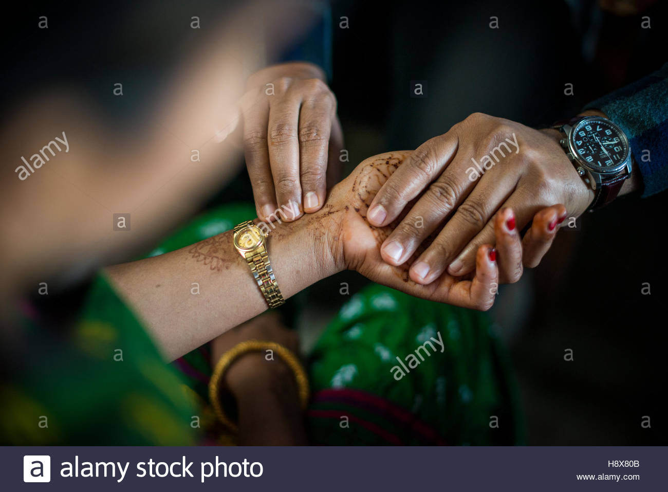 A doctor checks a woman's pulse with his fingers and times it on his watch in a small hospital in Nepal. - Stock Image