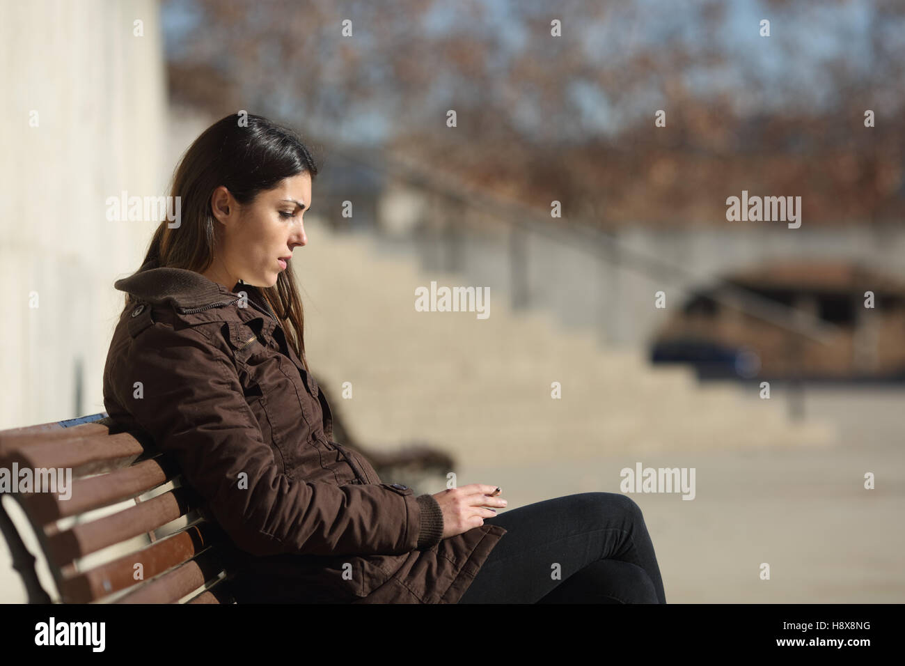 Side view of a sad pensive woman smoking sitting in a bench in the street in winter - Stock Image