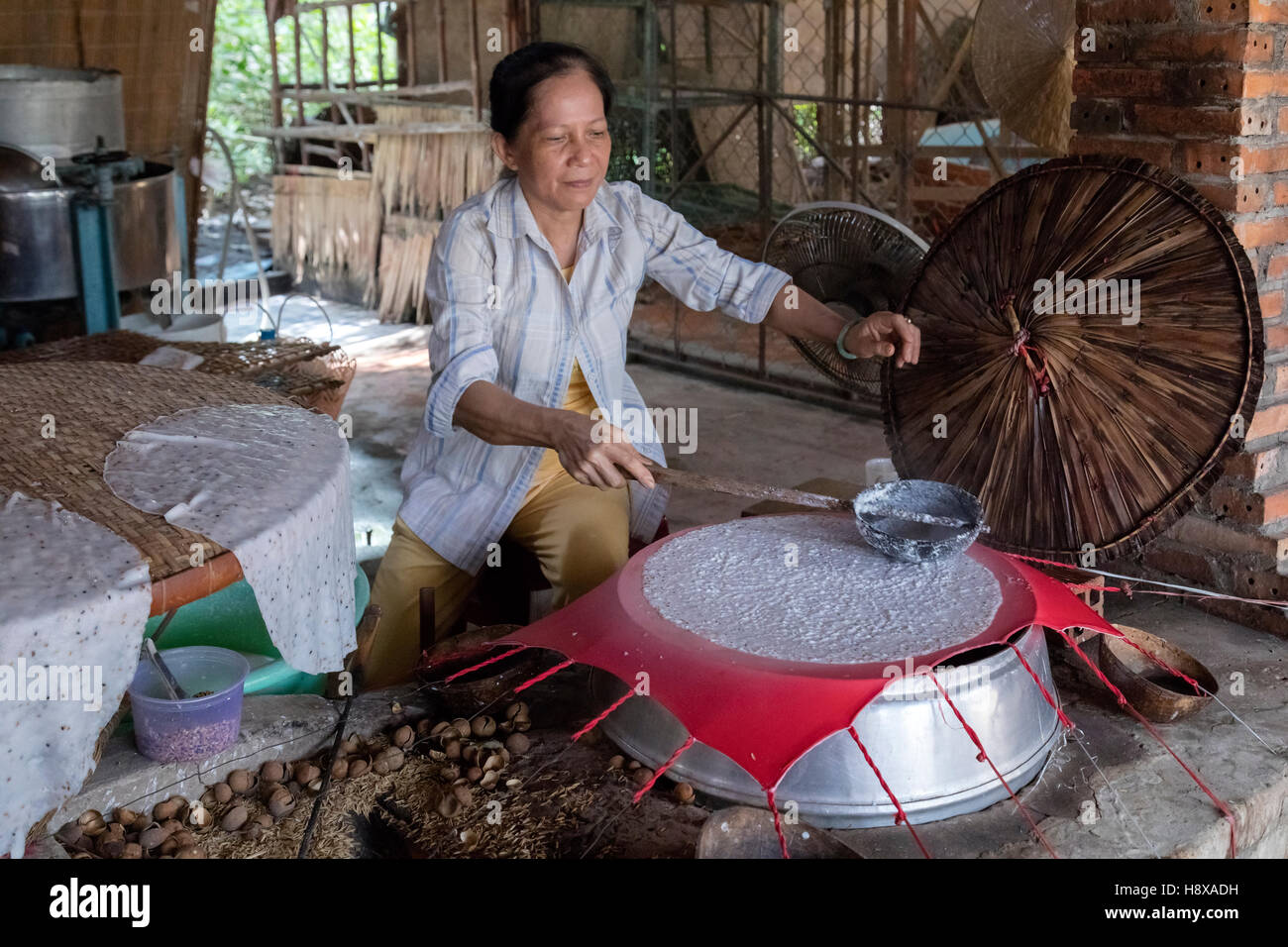 woman preparing rice noodles in Cai Be, Mekong Delta, Vietnam, Asia - Stock Image