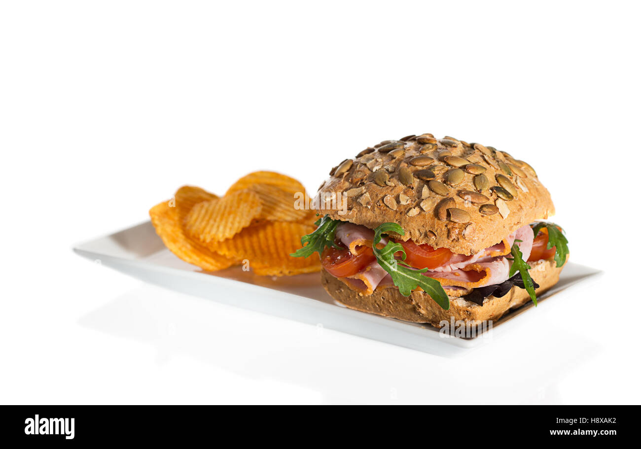 Ham salad roll with side serving of potato crisps - Stock Image