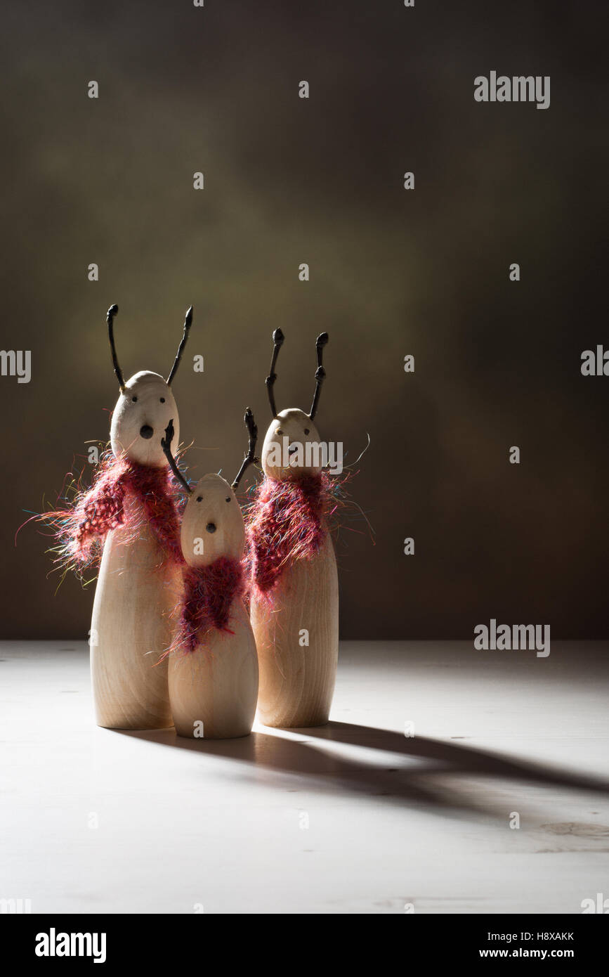 Creatively lit wooden reindeer animal figures with dark shadows - Stock Image