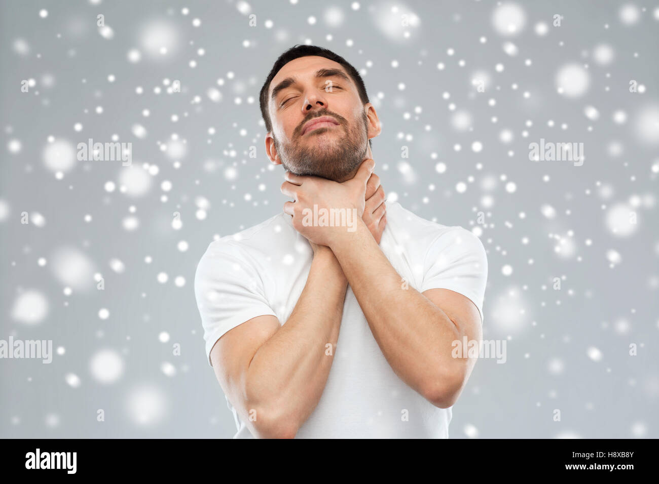 young man choking himself over snow background - Stock Image