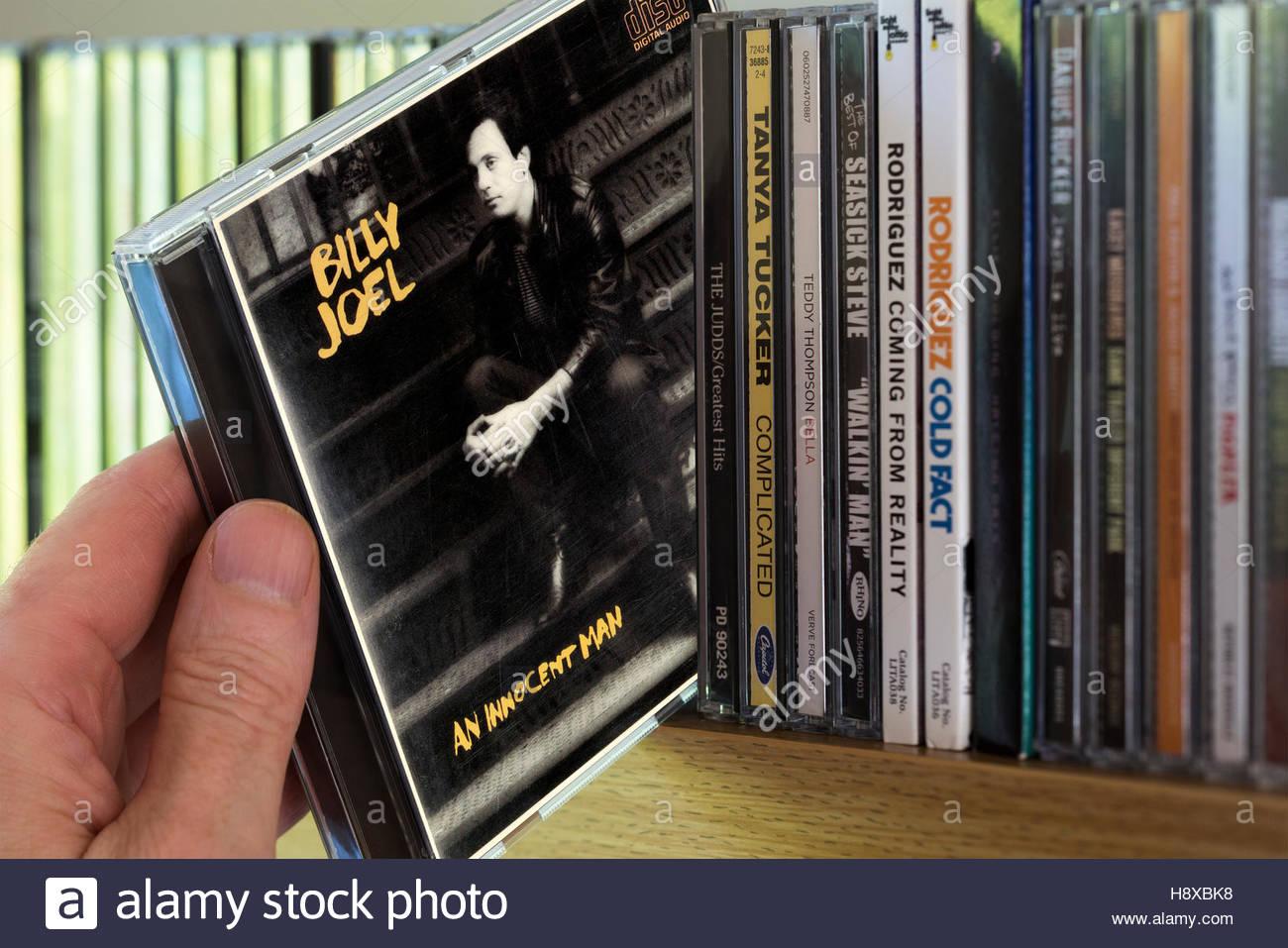 An Innocent Man, Billy Joel CD being chosen from a shelf of other CD's Stock Photo