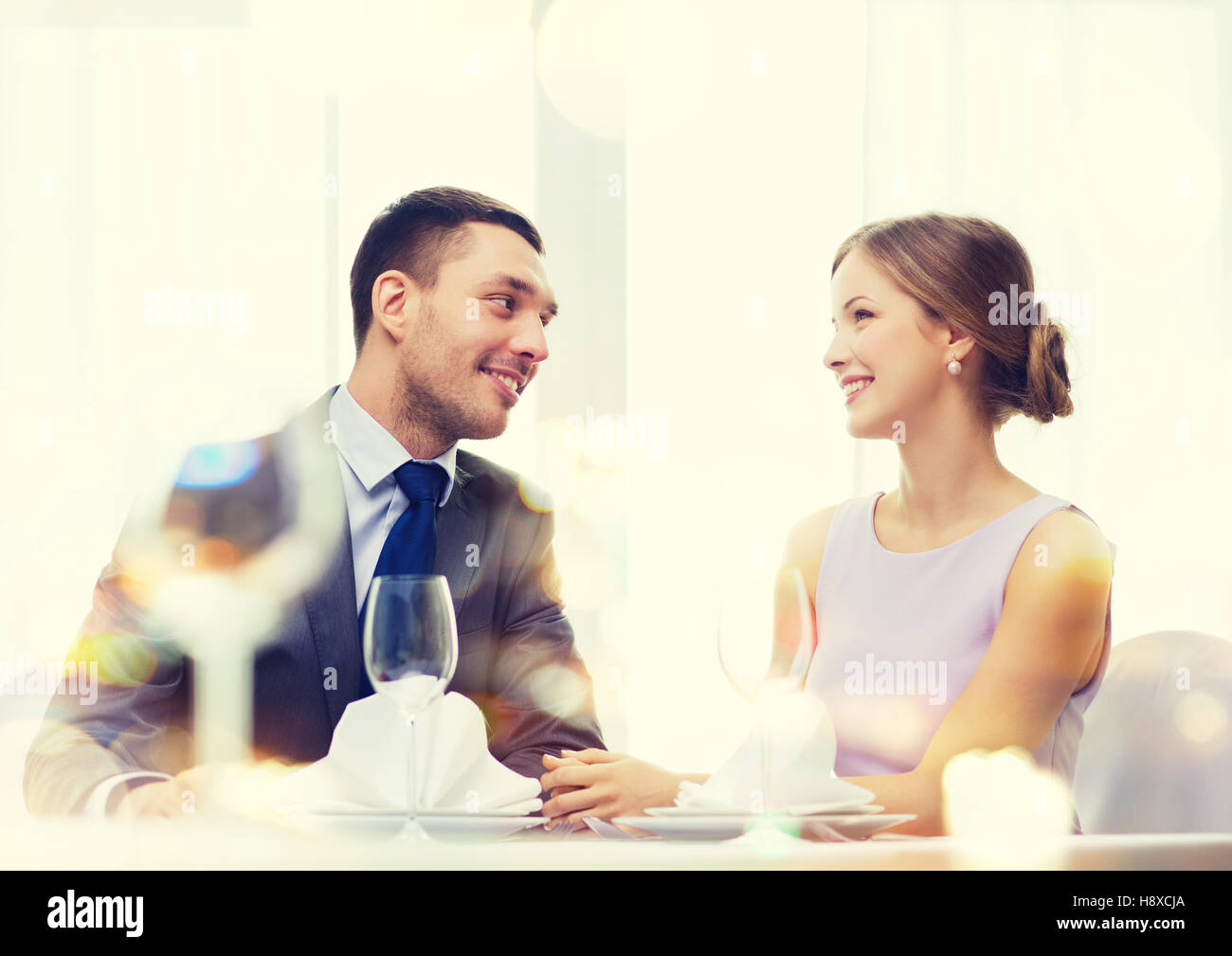 smiling couple looking at each other at restaurant Stock Photo