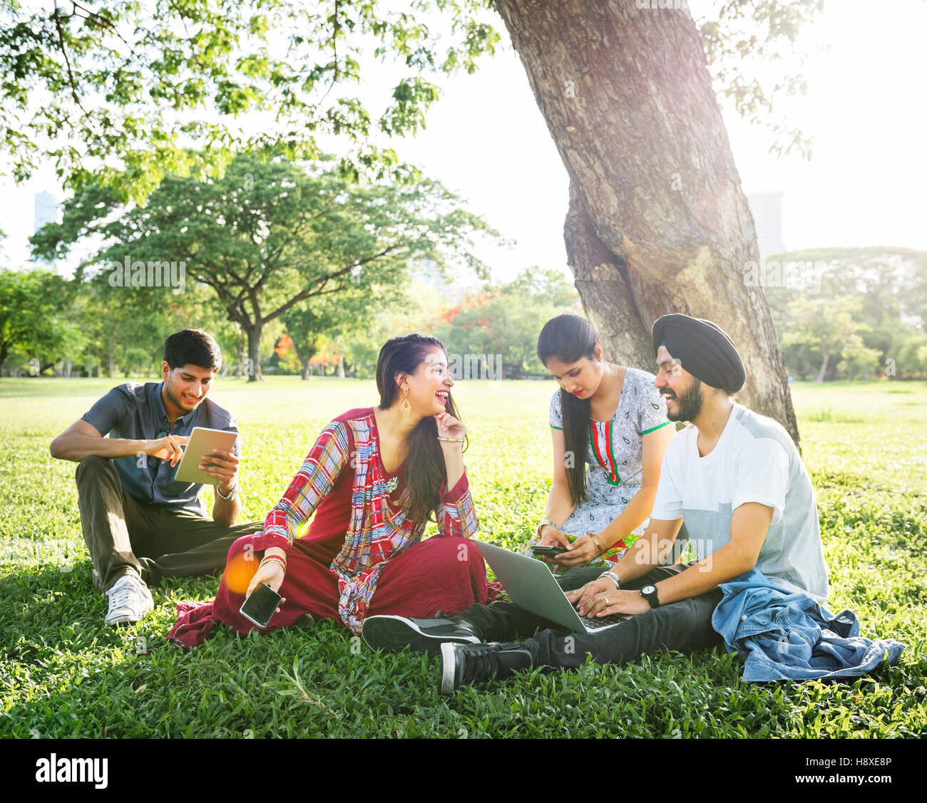 Friends Relaxing Sitting Park Gadgets Concept - Stock Image
