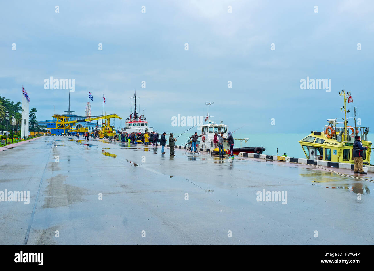 The foggy evening after the hard rain is the nice time for the fishing in port - Stock Image