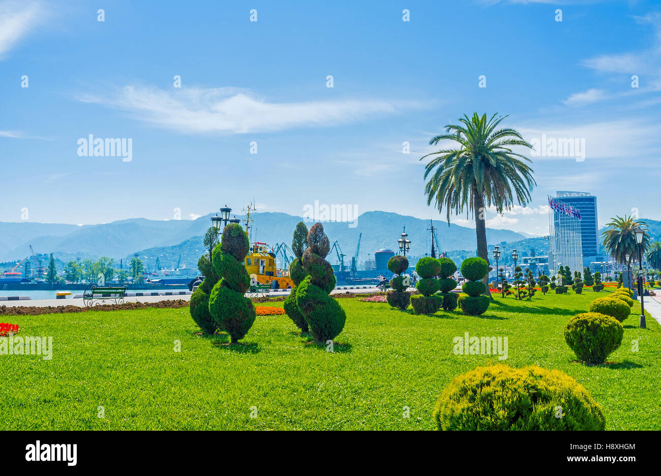 The ornamental French garden with the spiral trimmed trees and constructions of industrial port on the background, - Stock Image