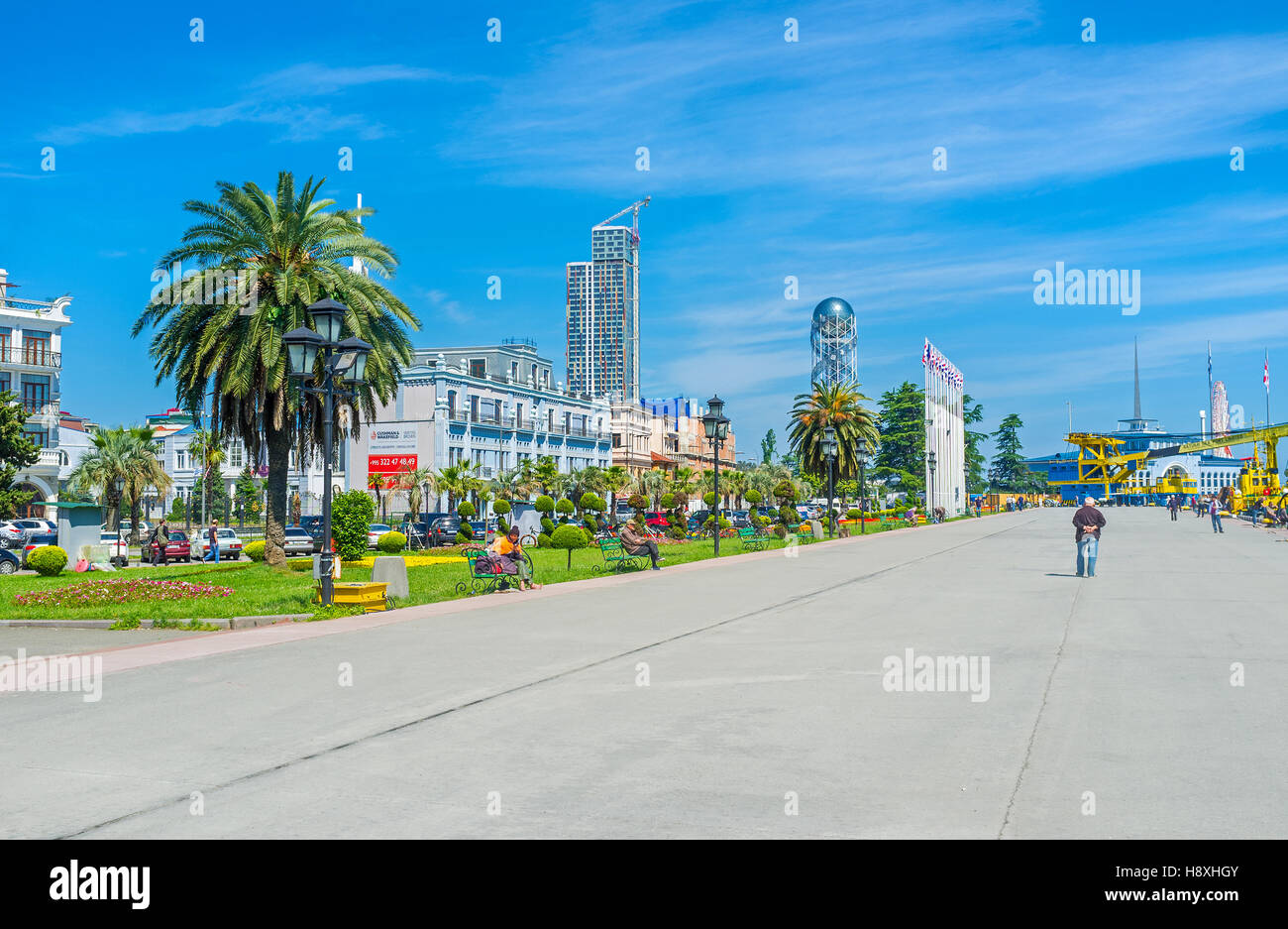 The seaside promenade with the beautiful French garden, decorated with flower beds, trimmed trees and lush palms - Stock Image